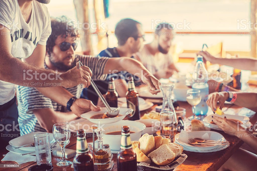 serving soup to his friends stock photo
