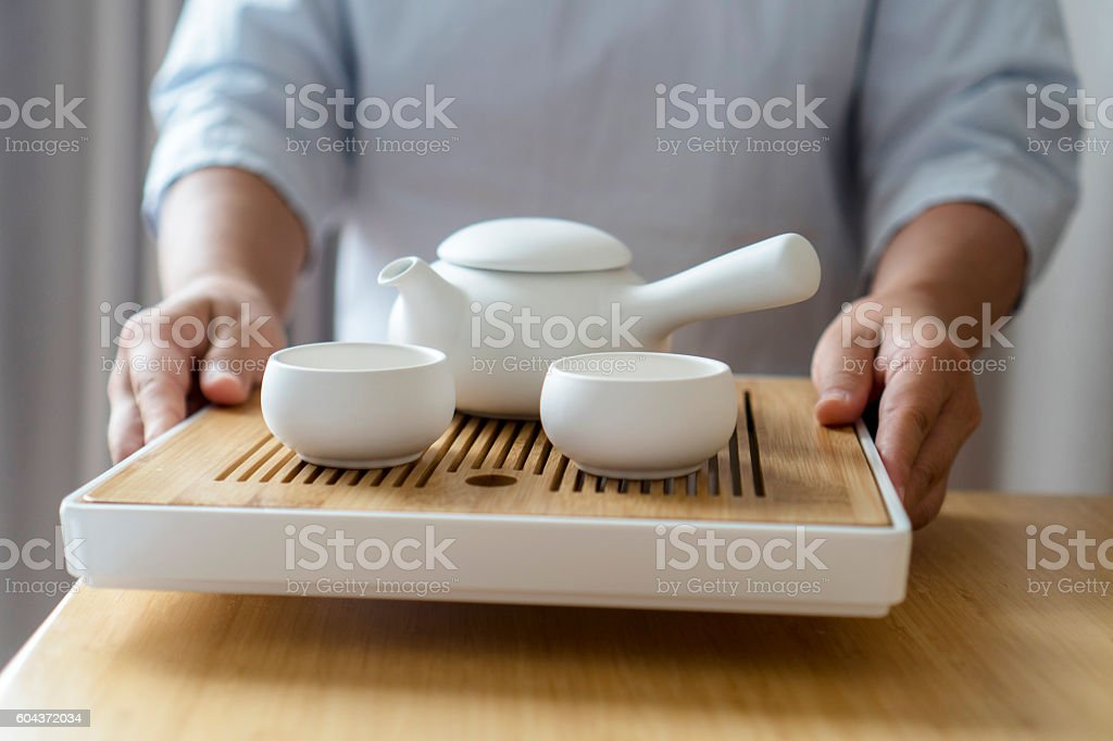 serving teapot and teacup on table stock photo