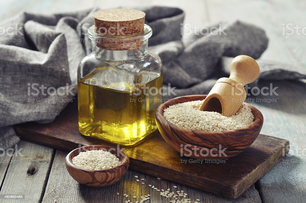 Sesame oil and seeds on wood board stock photo