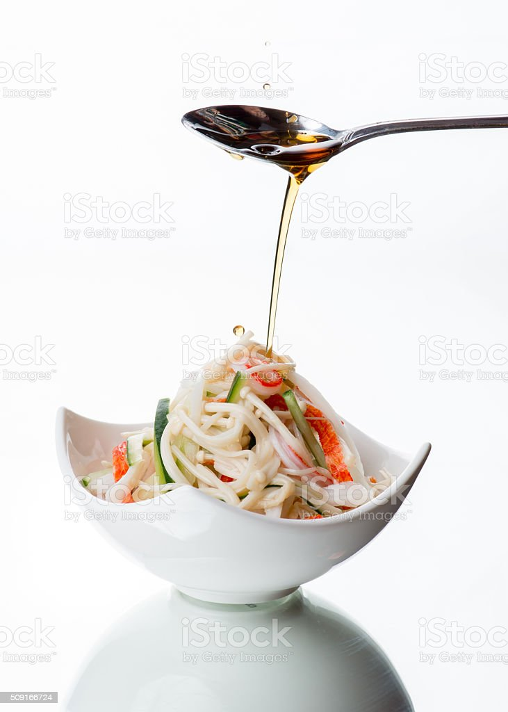 Sesame oil drizzled on Asian crab meat salad stock photo
