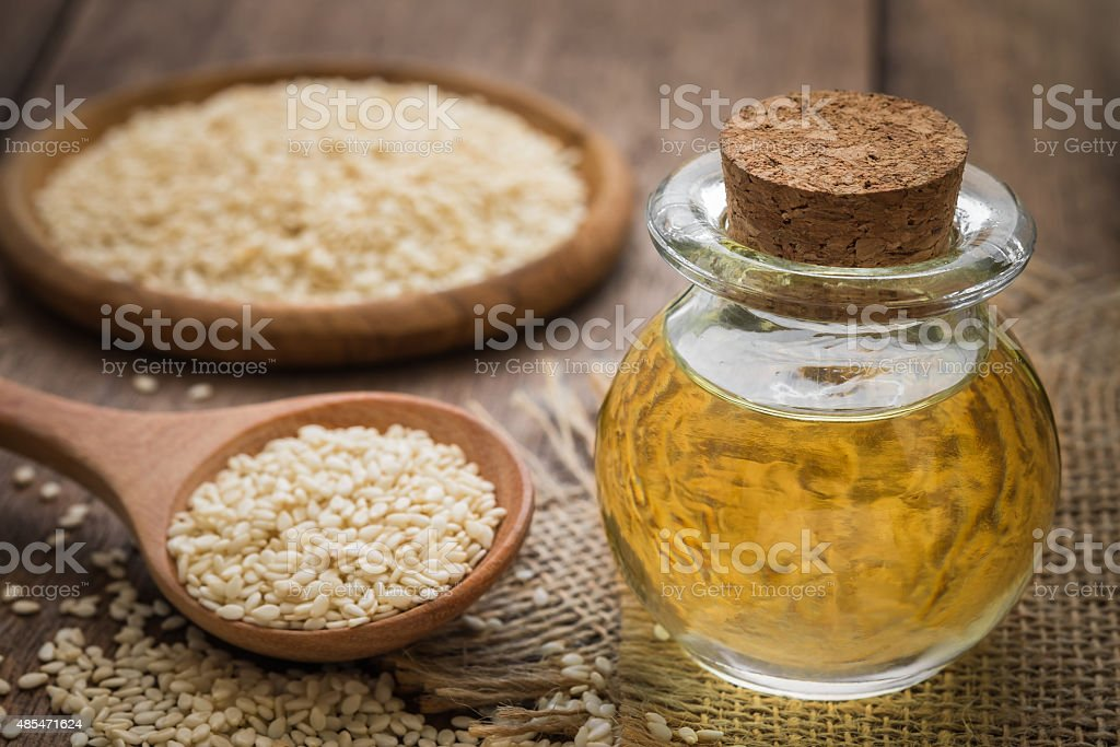 Sesame oil in glass jar and sesame seeds on spoon stock photo