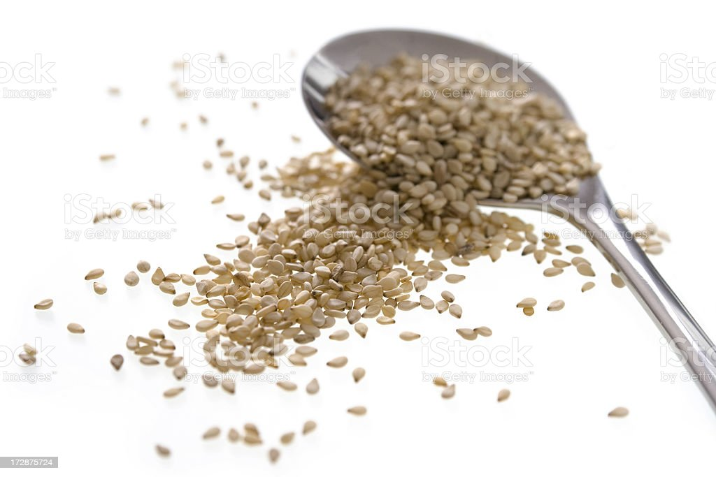 Sesame seeds and small serving spoon royalty-free stock photo