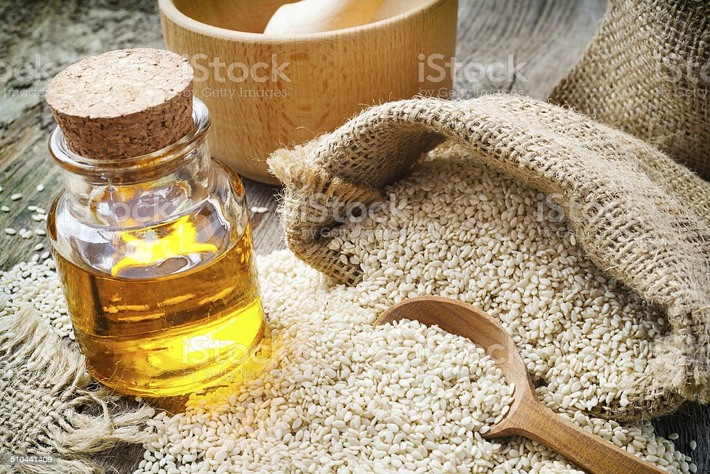 sesame seeds in sack and bottle of oil on  table stock photo