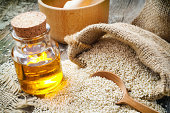 sesame seeds in sack and bottle of oil on  table