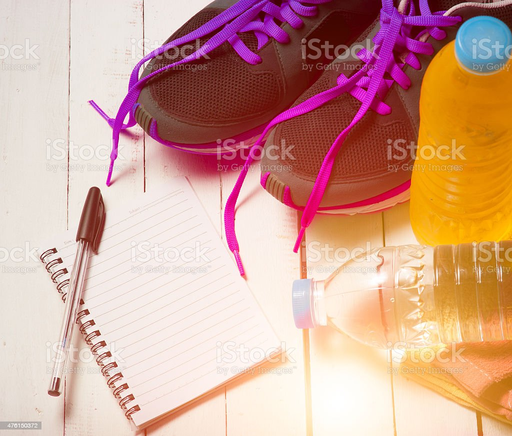 Set for sports activities and notebook on white wooden backgroun stock photo