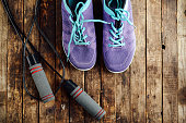 set for sports on wooden table, closeup. Rope and sneakers