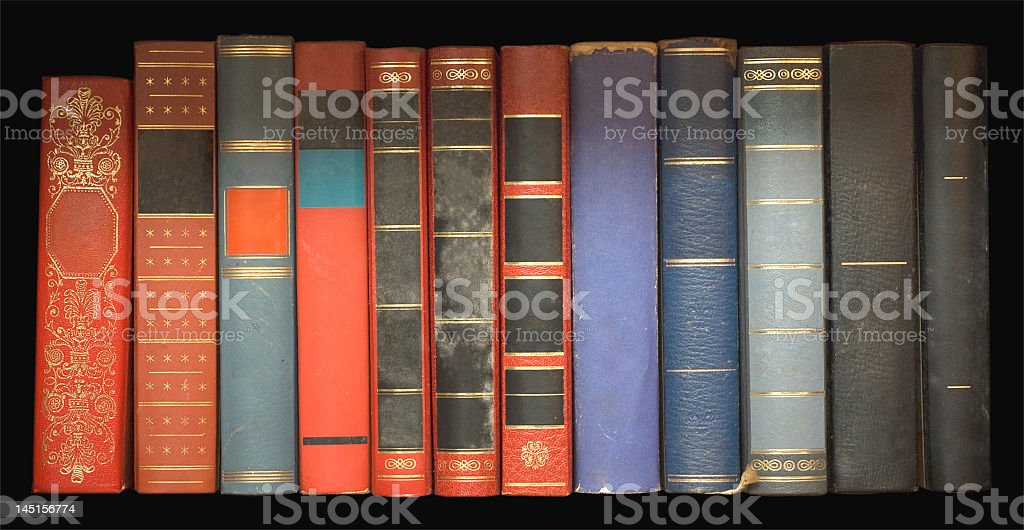 Set of antique books resting on a shelf stock photo