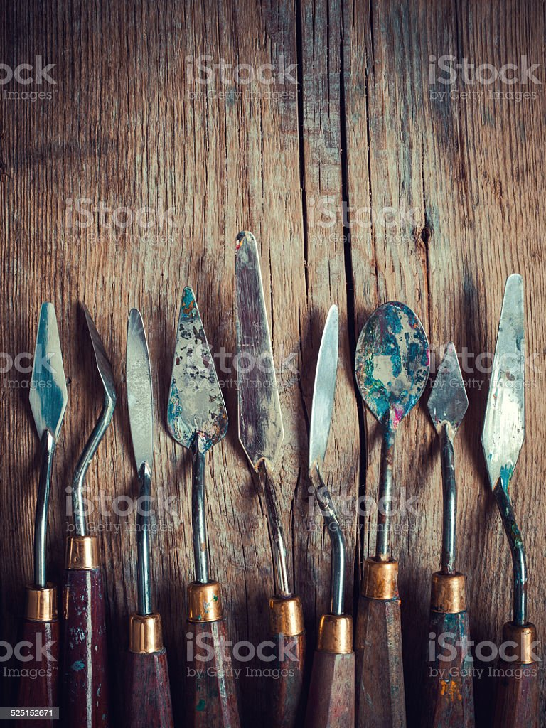 set of artist palette knifes on old wooden rustic table stock photo