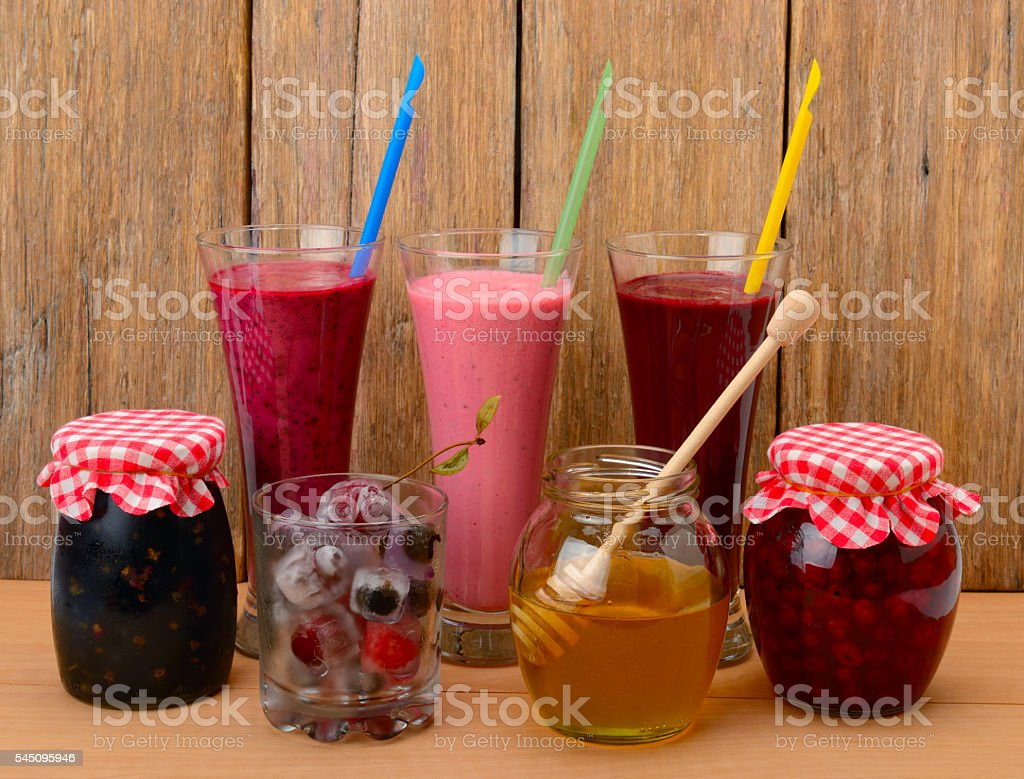 Set of berry smoothies, jams and frozen berries stock photo