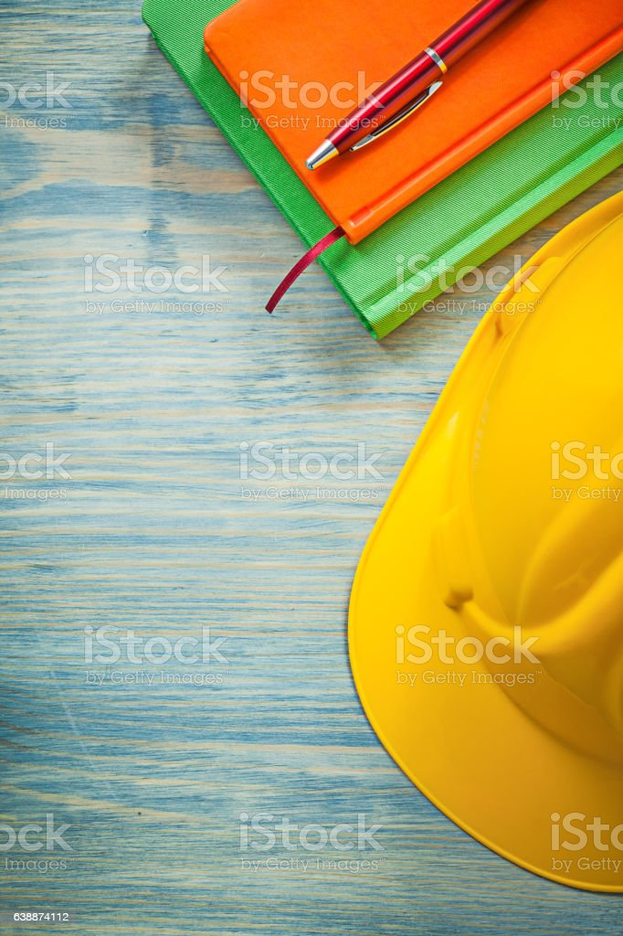 Set of building helmet notepads ballpoint pen on wood board stock photo