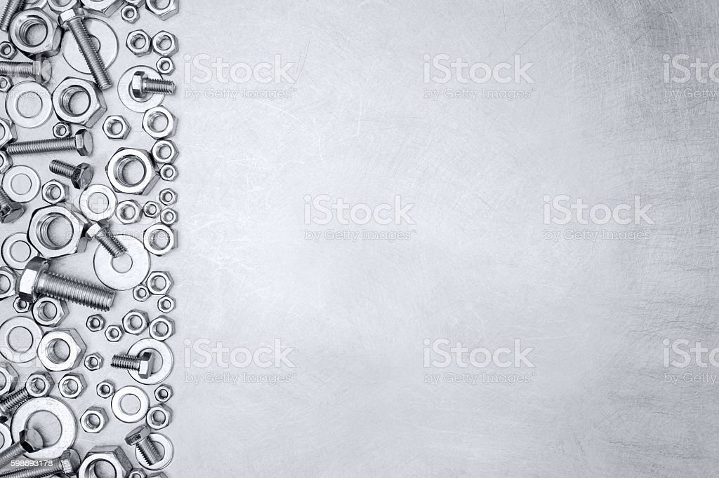 set of chrome screws and bolts on scratched metal background stock photo