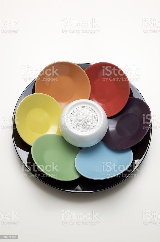 Set of colorful coffee saucers arranged around a sugar cup royalty-free stock photo