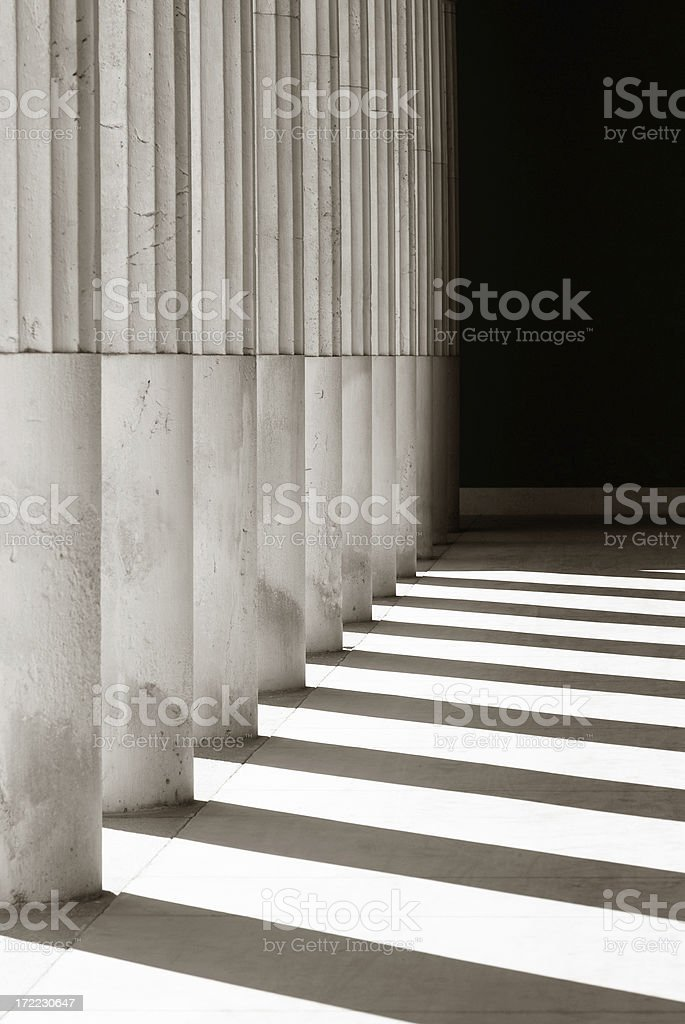 A set of columns and their shadows in the sun stock photo