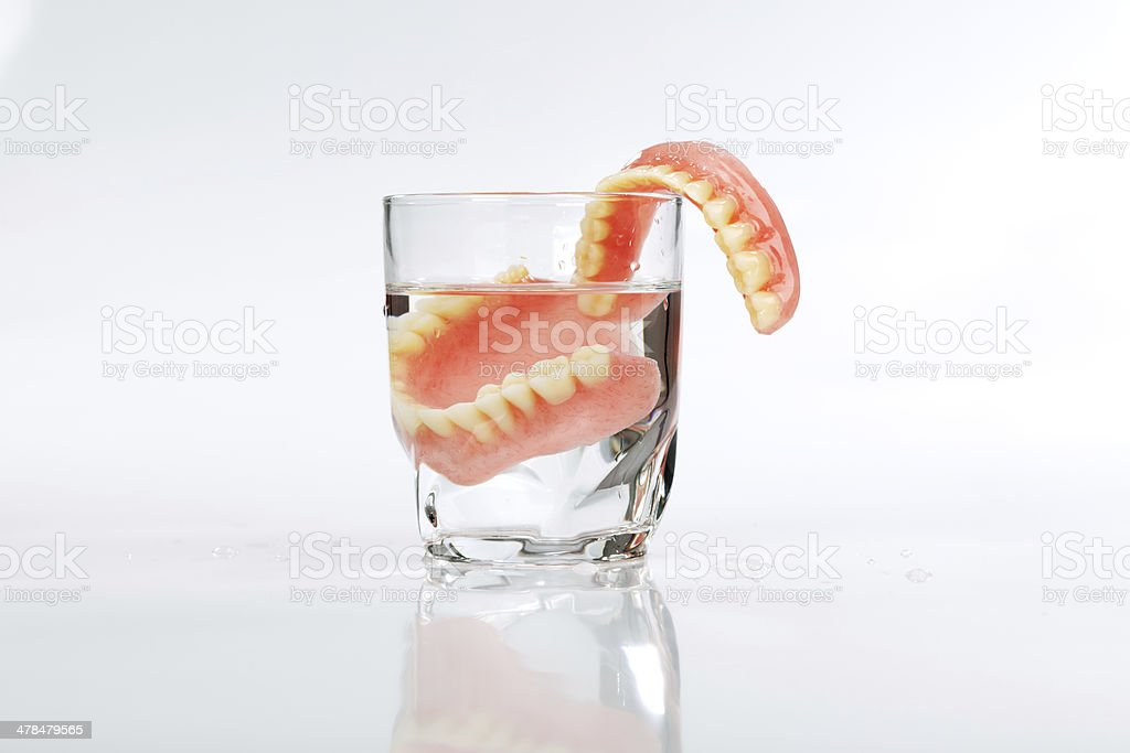 Set of dentures in a glass of water stock photo