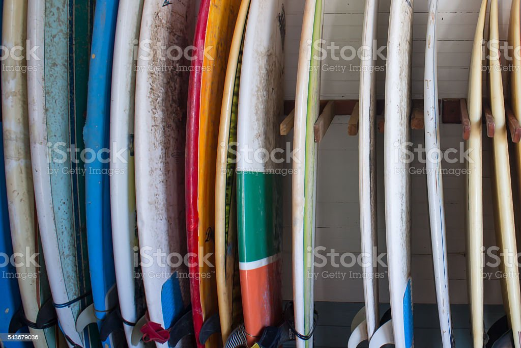 Set of different color surf boards in a stack stock photo