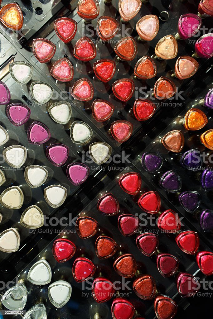 Set of different nail varnishes on shelves in cosmetic store stock photo