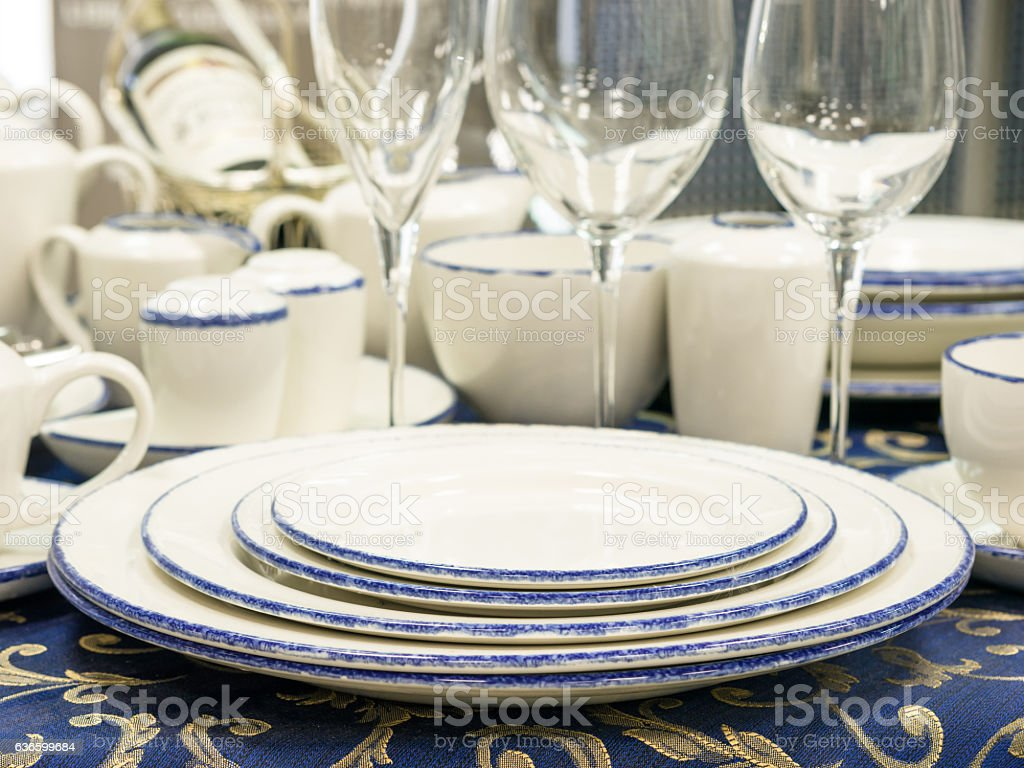 Set of new dishes on table with blue tablecloth. Stack of plates,...