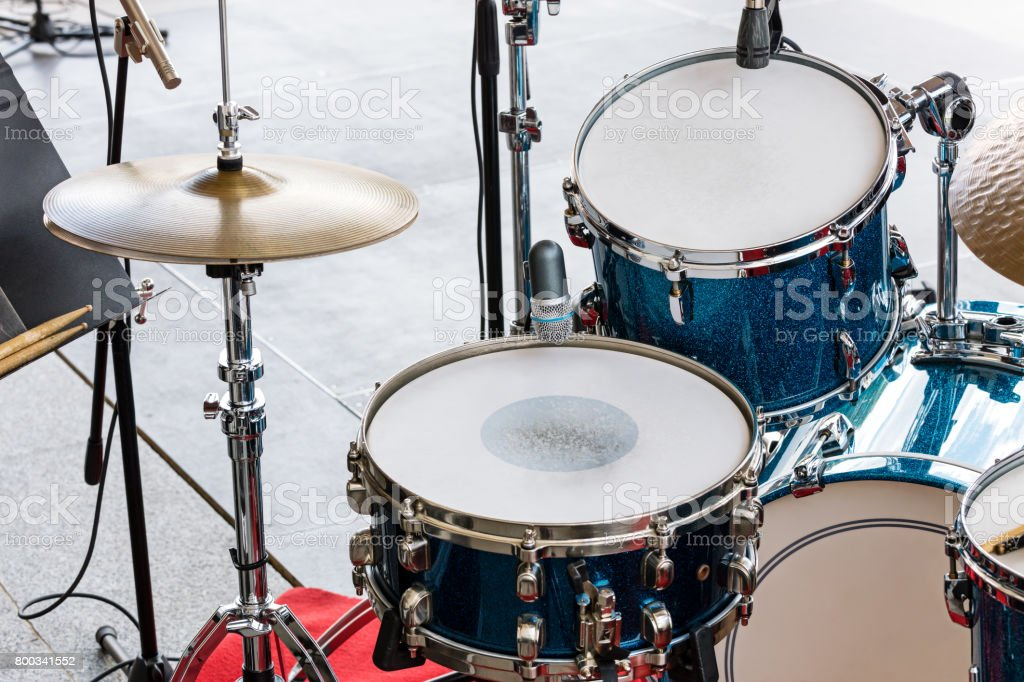 set of drums, cymbals and microphones on pavement background stock photo