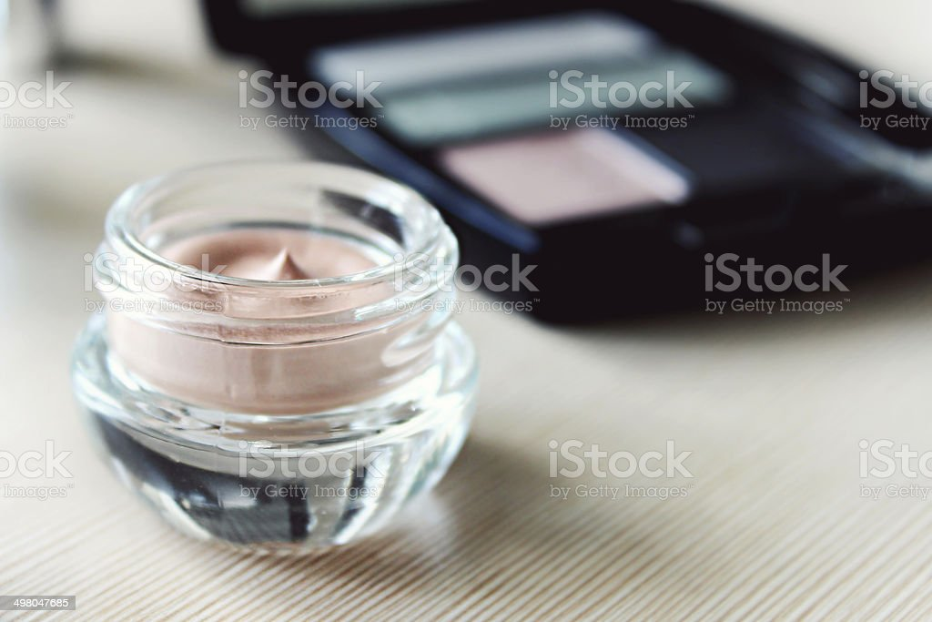 Set of eyeshadow and a cream primer on a dressing table stock photo