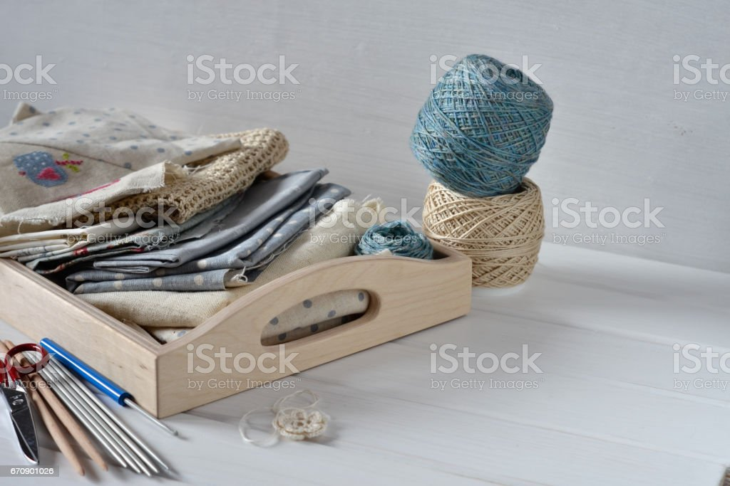 Set of fabric, ribbons and tools for sewing and needlework in wooden box. stock photo