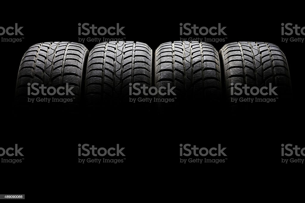 Set of four black car tires lined up horizontally stock photo