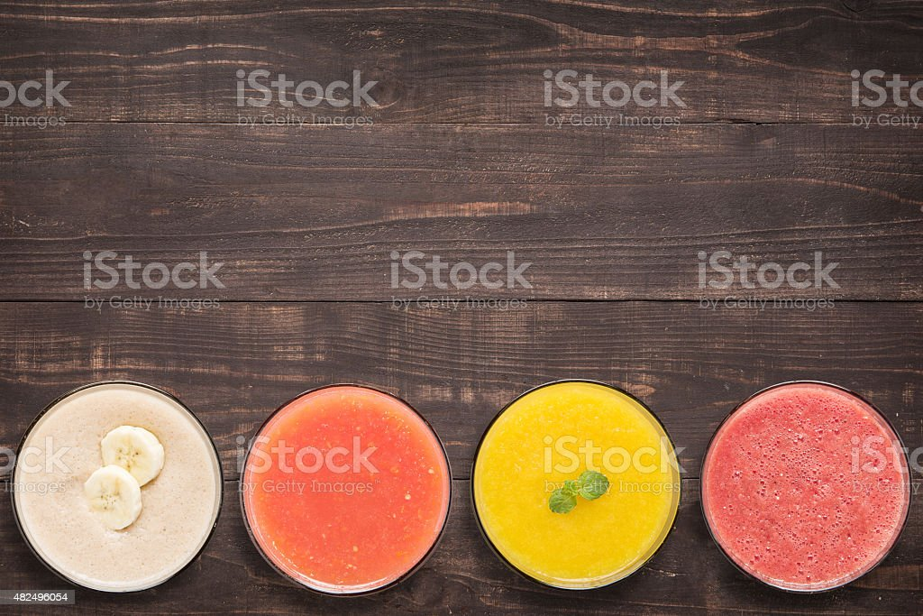 Set of fruit smoothie and juice in glasses on wooden stock photo