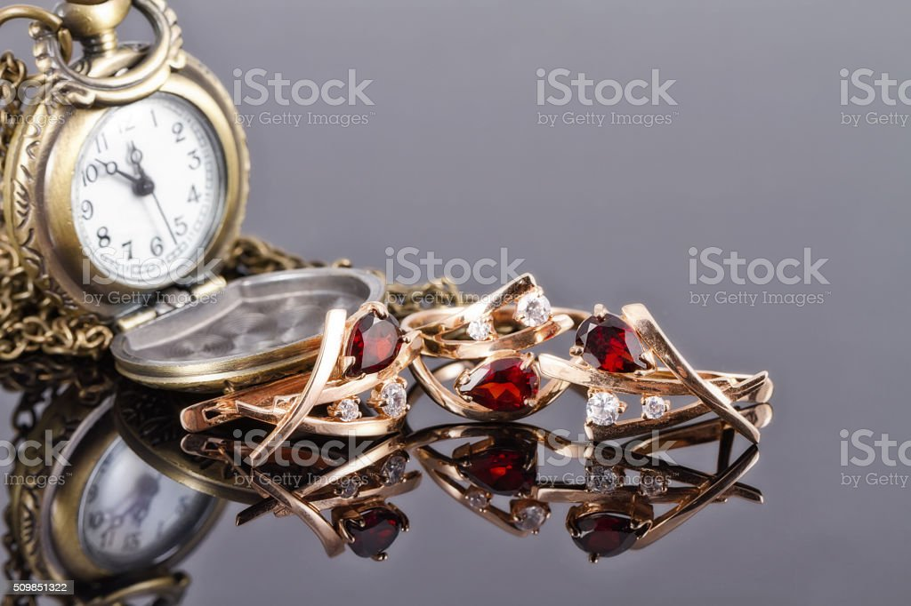 set of gold jewelry with rubies and copper pocket watch stock photo