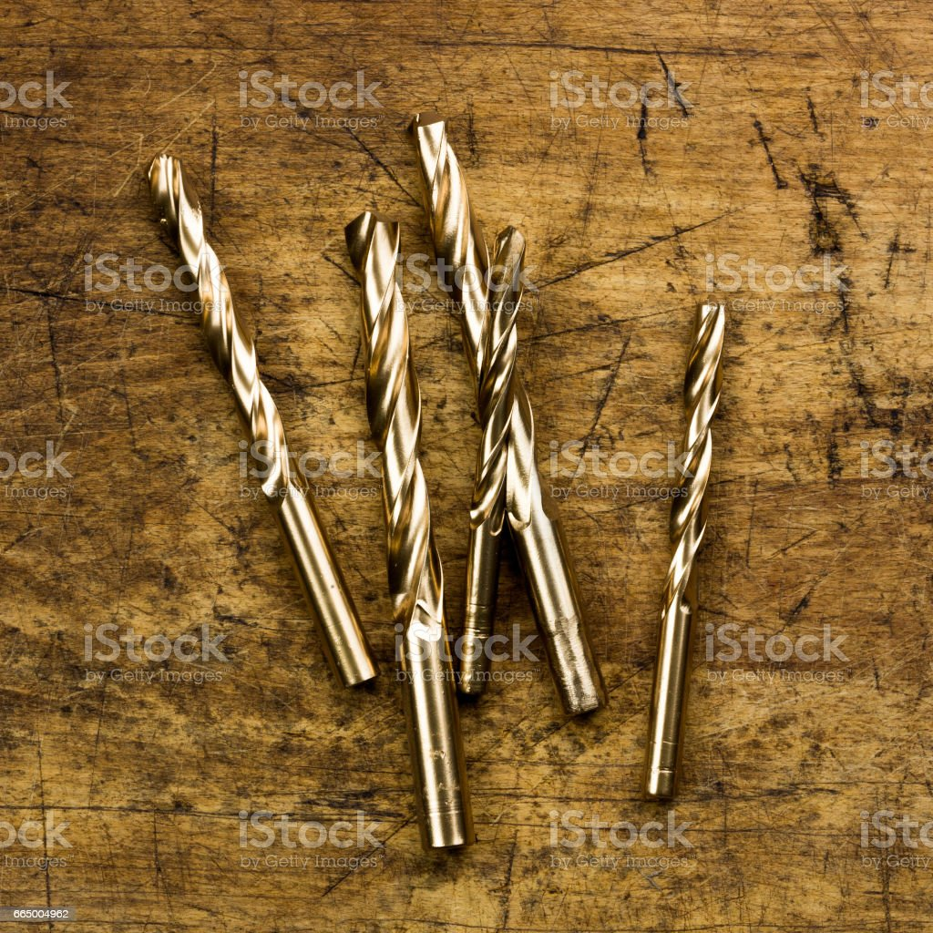 Set of golden drill bits on wooden background. Symbolic repair t stock photo
