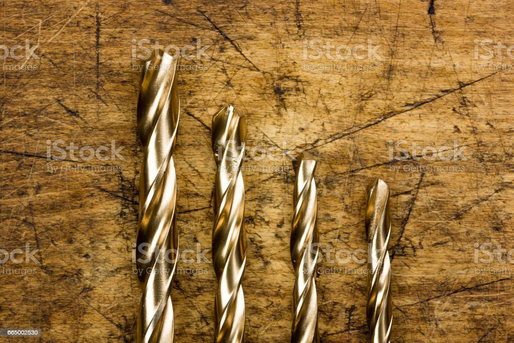 Set of golden drill bits on wooden background. Symbolic repair tool stock photo