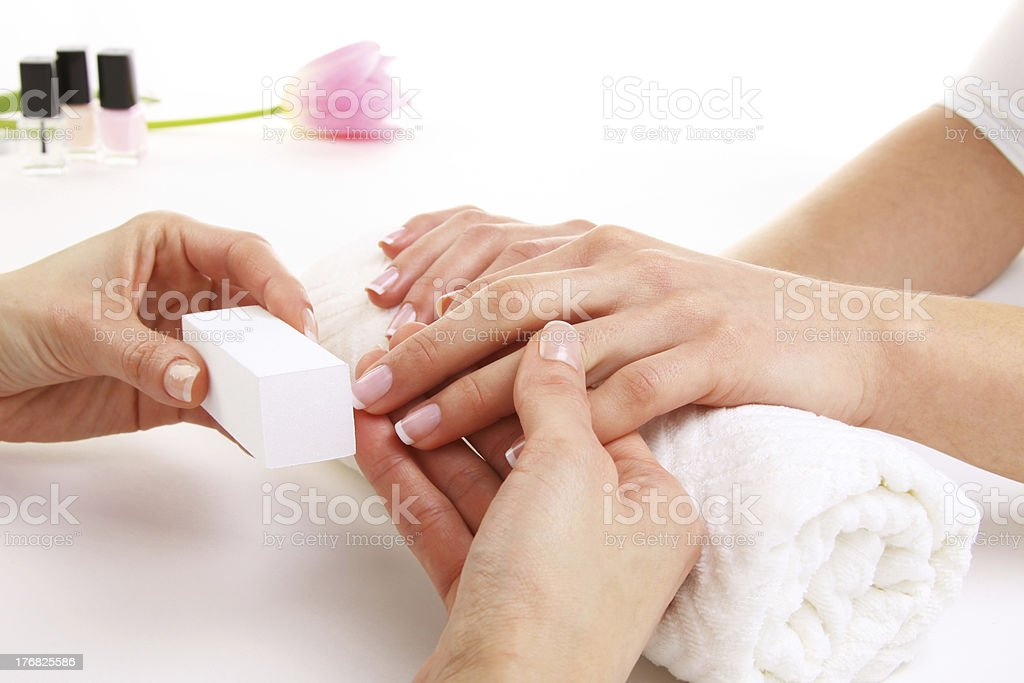 A set of hands receiving a manicure treatment on a towel royalty-free stock photo