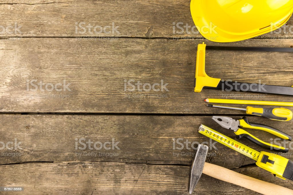 Set of industrial work tools arranged on a rustic wooden table stock photo
