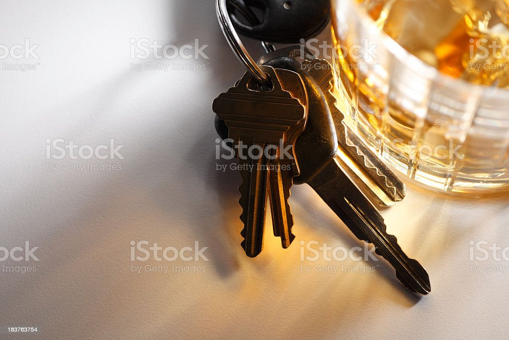 Set of keys sitting at base of glass of alcohol royalty-free stock photo