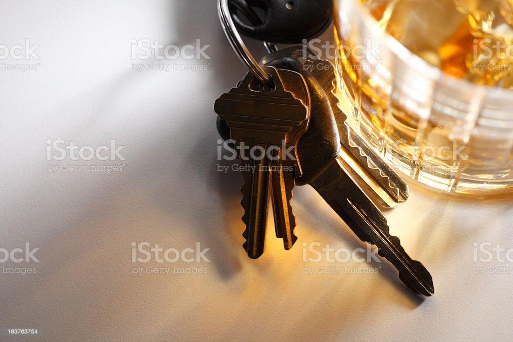 Set of keys sitting at base of glass of alcohol stock photo