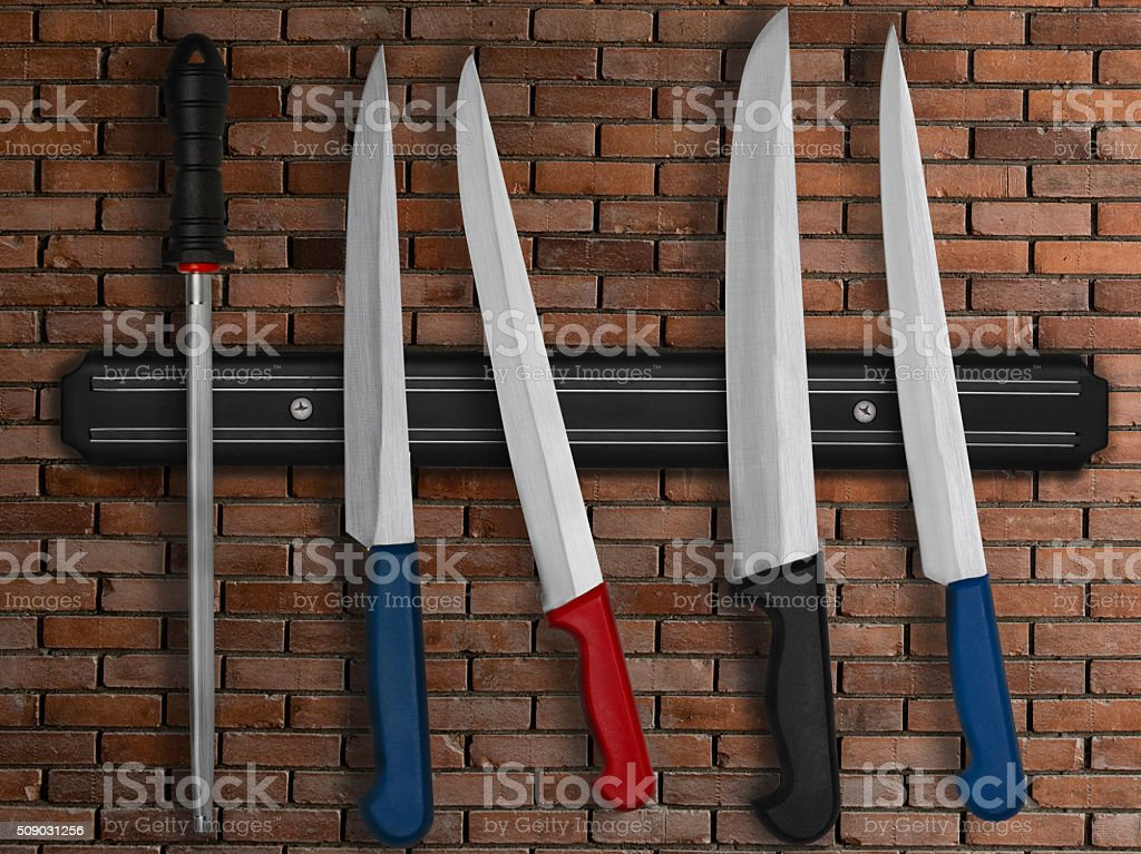 Set of kitchen knives on magnetic holder stock photo