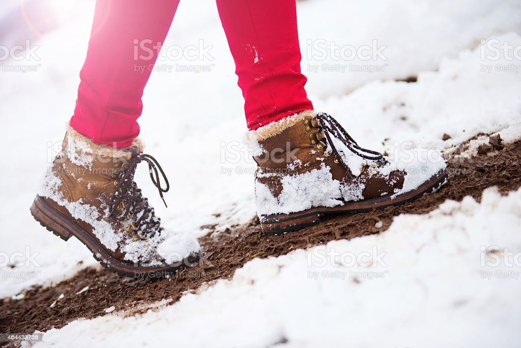 A set of legs in red pants and hiking boots in snow stock photo