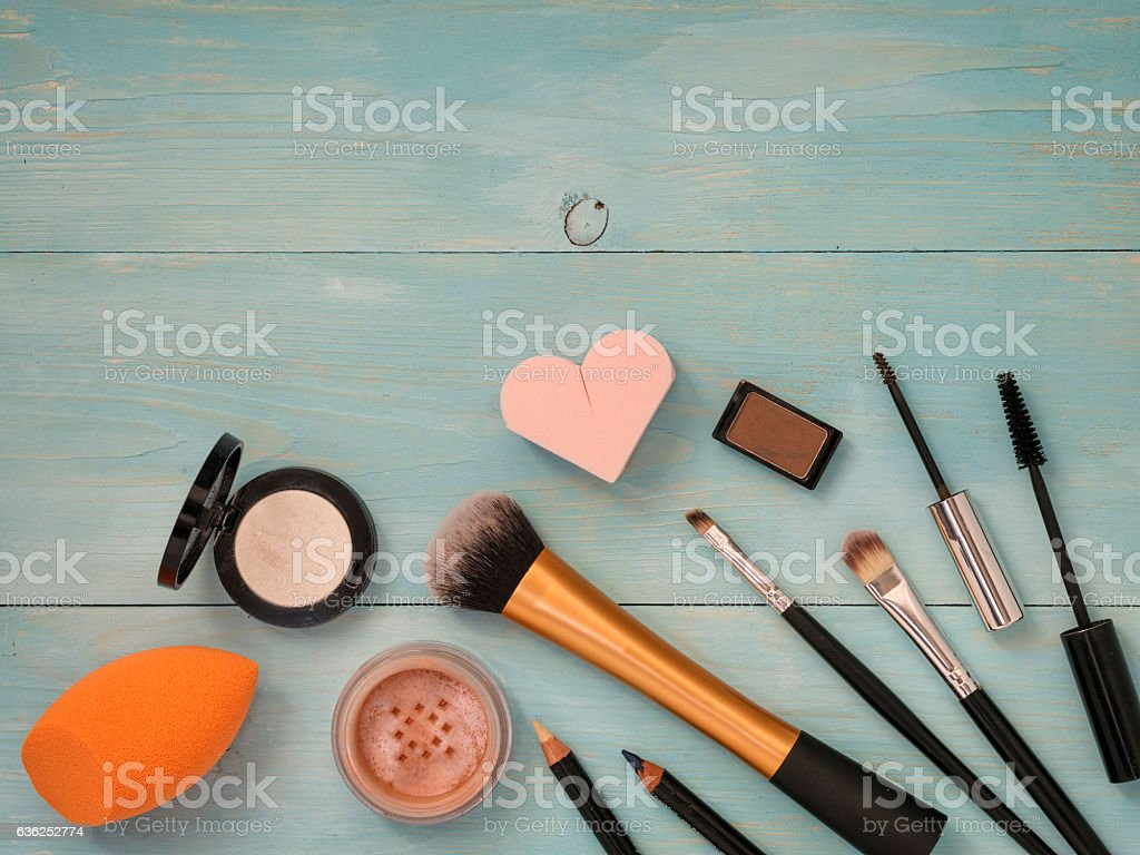 Set of makeup on turquoise wooden background stock photo