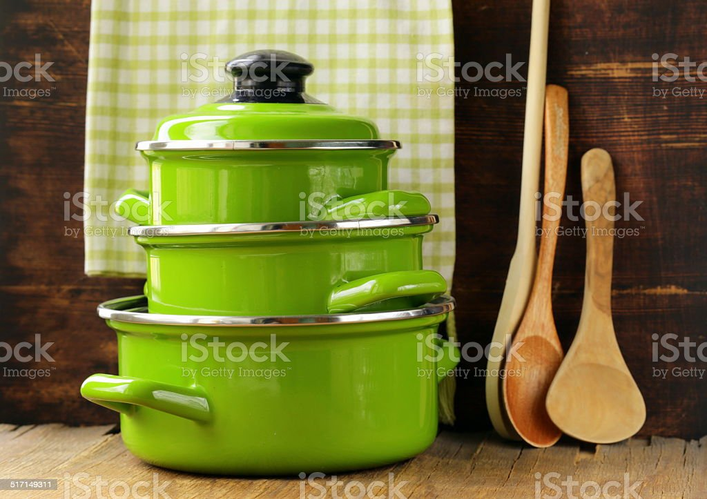 set of metal green pots cookware on a wooden background stock photo