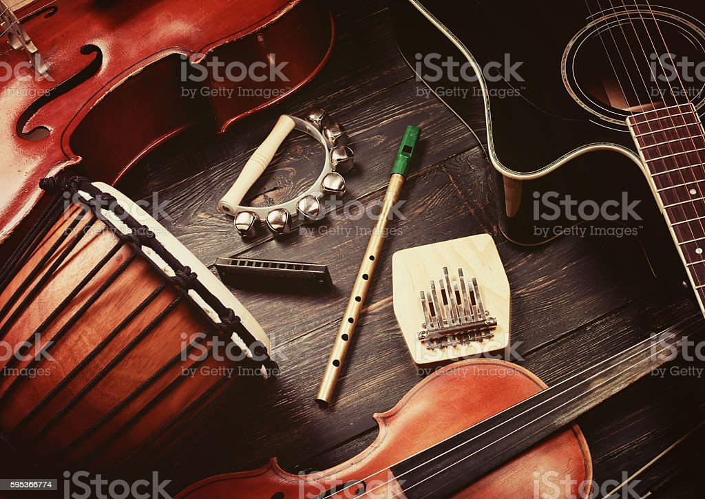Set of musical instruments on dark wooden background: guitar, violin,...