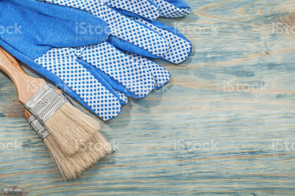 Set of paintbrushes safety gloves on wooden board construction c stock photo