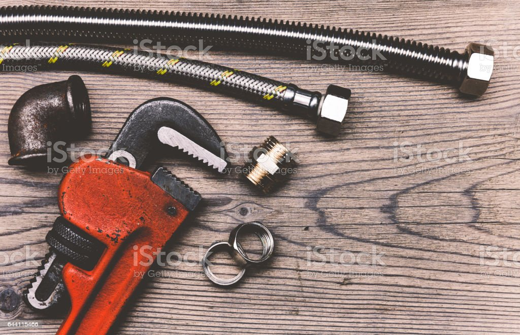 Set of pipes plumbing tools fittings on wooden background stock photo
