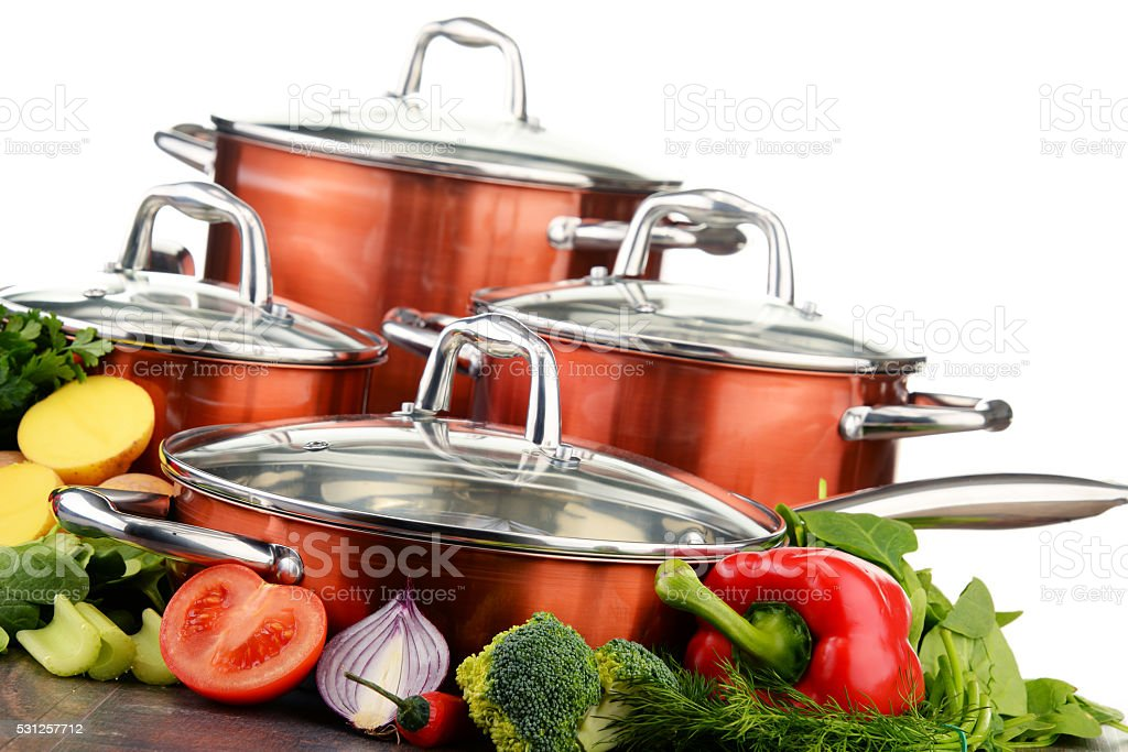 Set of pots and raw vegetables isolated on white background stock photo