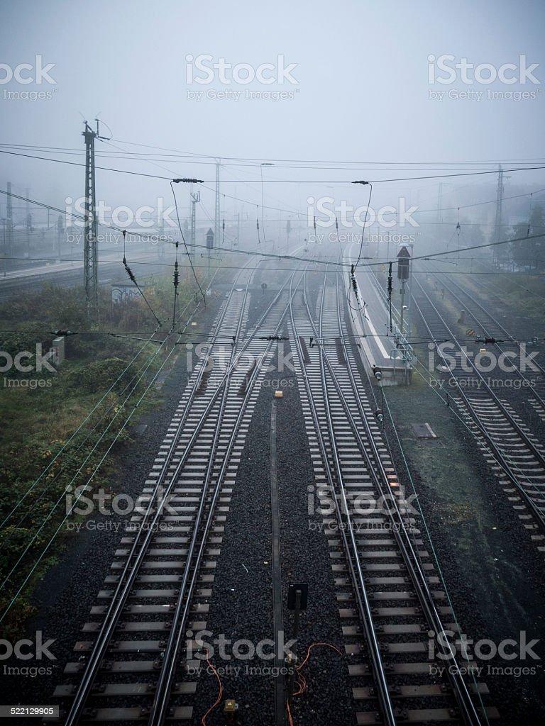 Set of rails leading into the grey morning fog stock photo
