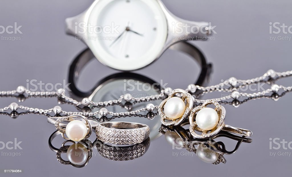 Set of silver jewelry with pearls and women's watches stock photo