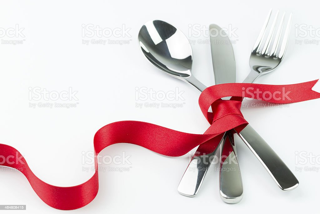 Set of silverware tied up with a red ribbon stock photo