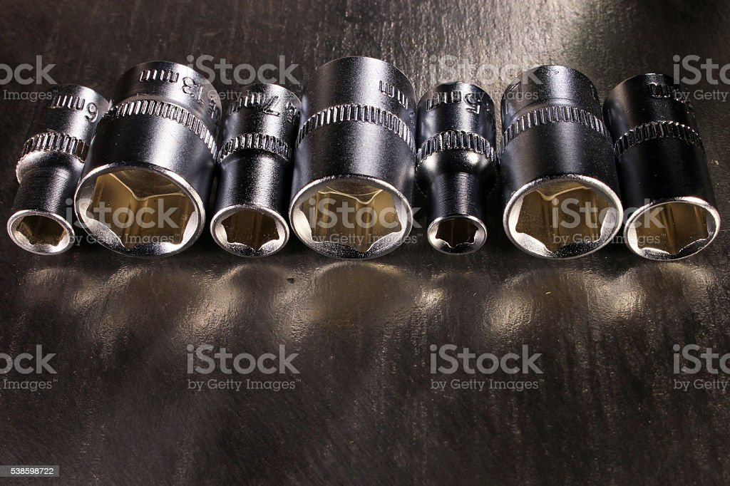 Set of stainless steel hex sockets on shiny metal surface stock photo