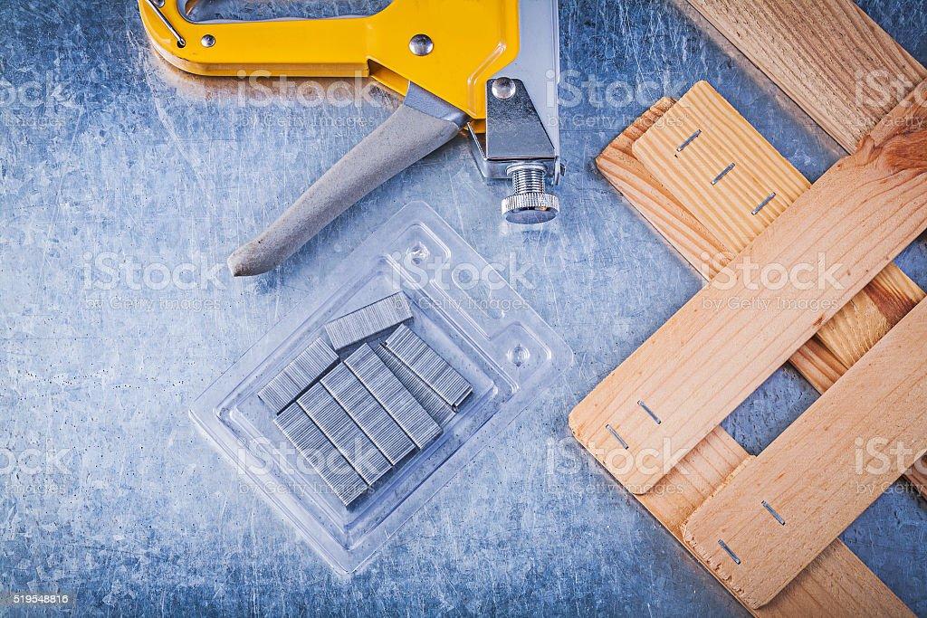 Set of stapler gun chrome staples wooden building board on stock photo