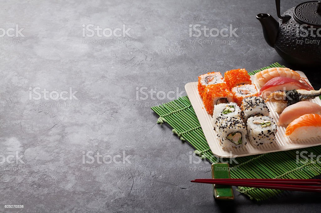 Set of sushi and maki roll and green tea stock photo