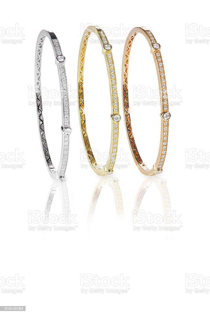 Set of three colored gold diamond bangle bracelets standing upri stock photo