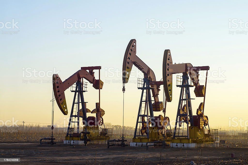 Set of three pump jacks in an isolated area at sunset stock photo
