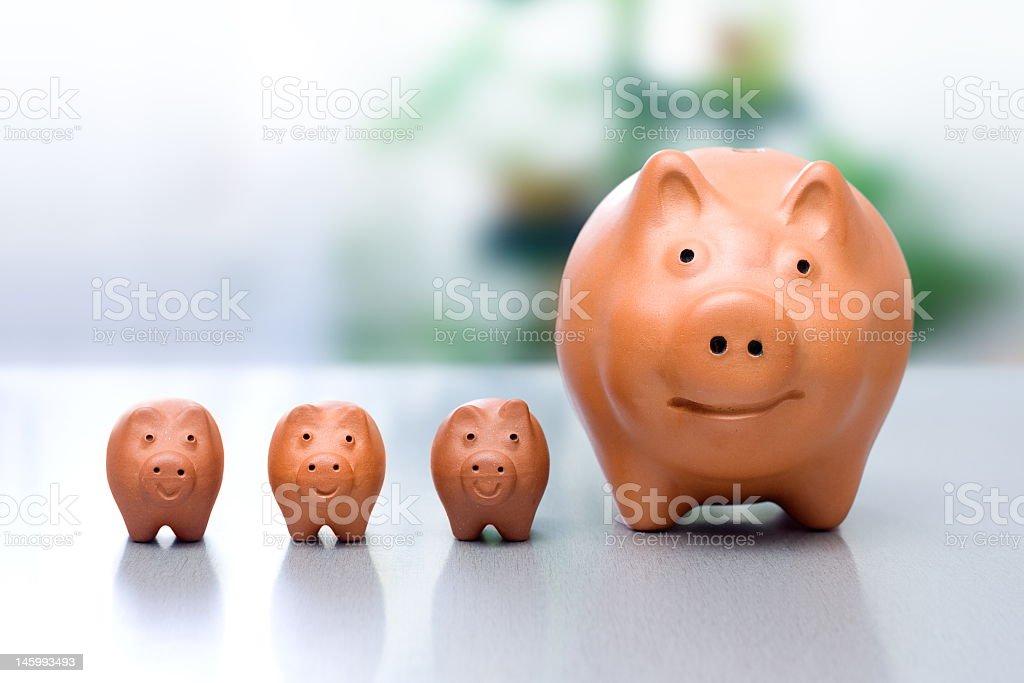 Set of three small and one large orange piggy banks stock photo
